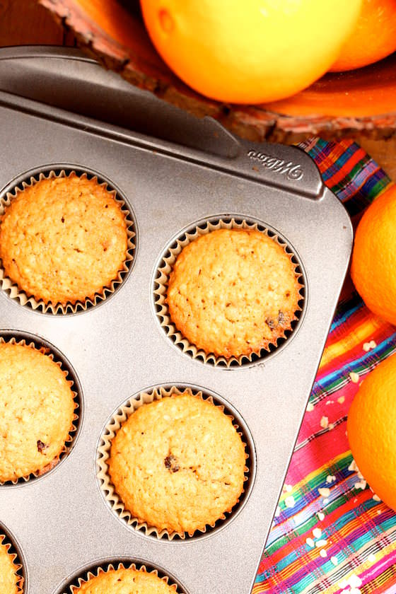 muffins in muffin tin, colourful tablecloth, oranges