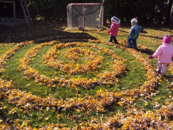 toddlers walking in fall leaf labyrinth in backyard