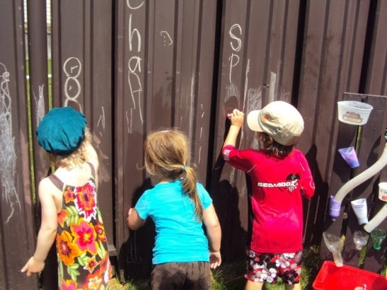 preschoolers drawing with chalk on brown metal fence