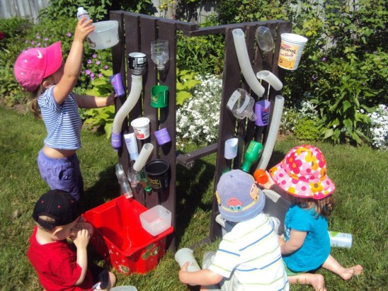 Toddlers pouring water at homemade water wall