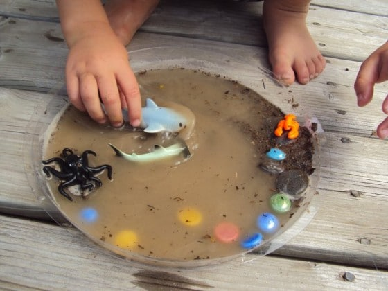 small world play idea in a plant pot with water and plastic animals