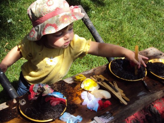 toddler making mud pies in wheelbarrow