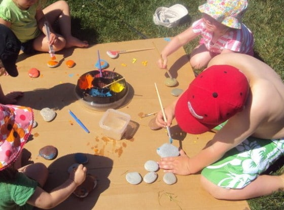 kids painting on stones in backyard