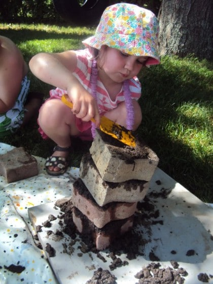 preschooler stacking bricks troweled with mud