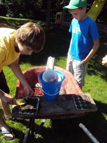 boys playing in wheelbarrow mud kitchen