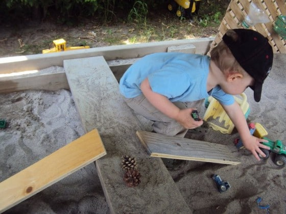 boards in the sandbox become ramps, benches, stove-tops and work benches