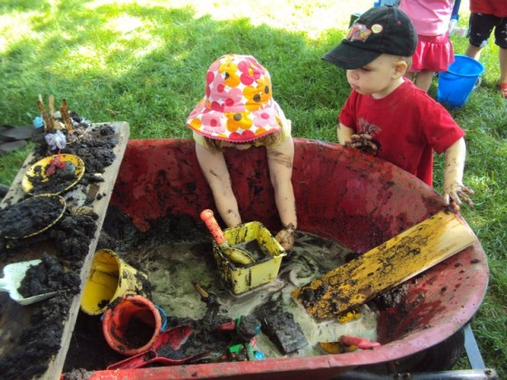 kids playing in wheelbarrow filled with mud