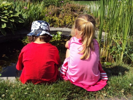 preschool boy red shirt, preschool girl pink shirt, sitting beside backyard pond