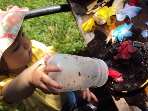 toddler pouring water on mud pie