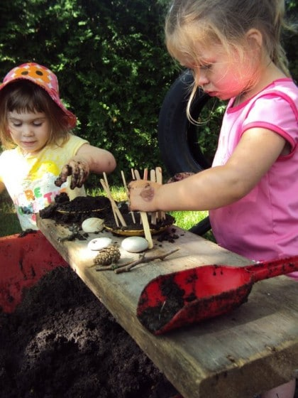 kids using a wheelbarrow as a mud patch