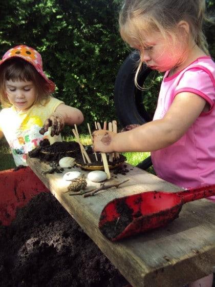 kids using a wheelbarrow as a mud patch