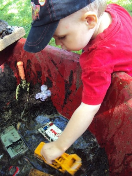 Child playing with cars in mobile mud patch