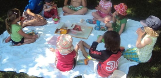 9 toddlers and preschoolers eating lunch on blanket in backyard