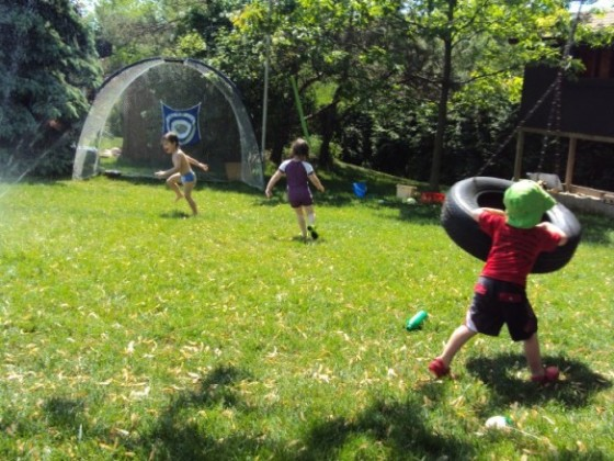 3 preschoolers running through sprinkler in backyard
