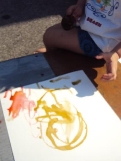 Child making art with coloured ice