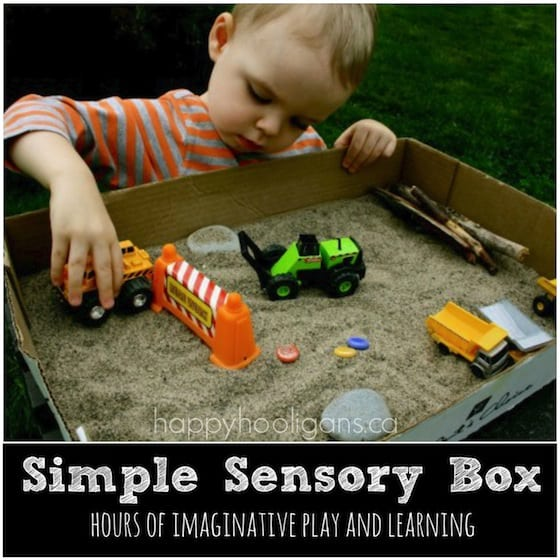 Construction sensory bin - cardboard box, sand and toy trucks