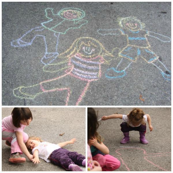 Kids tracing their bodies with sidewalk chalk