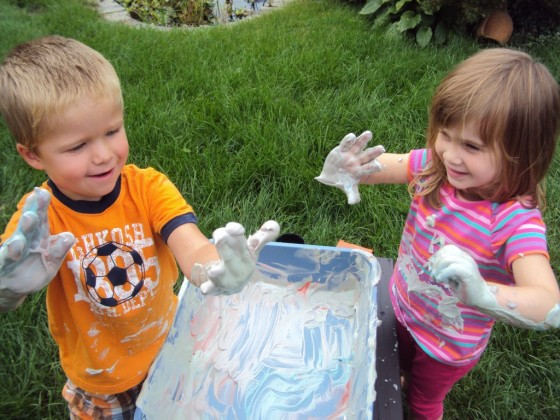 toddlers playing with shaving cream sensory bin