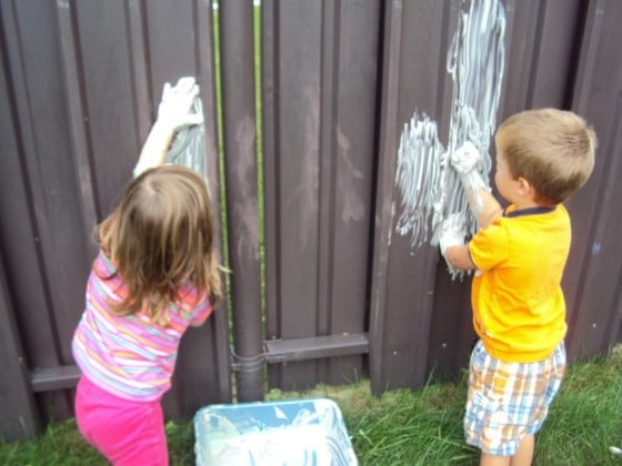 kids painting on fence with shaving cream