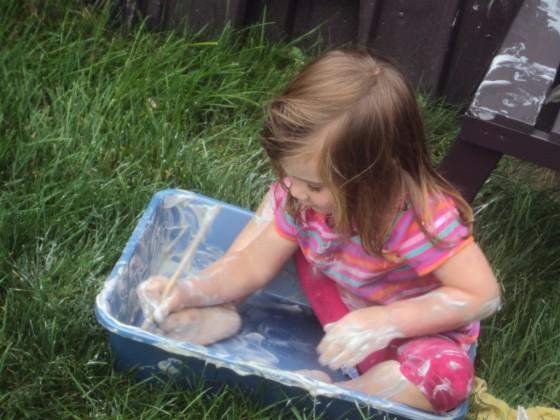 Child playing in bin of shaving cream