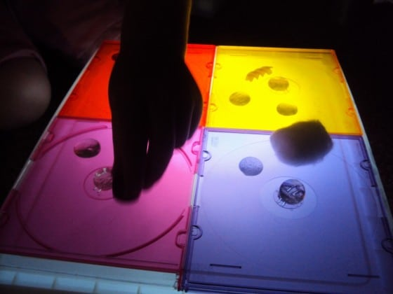 Coloured CD cases for play on a DIY light box.