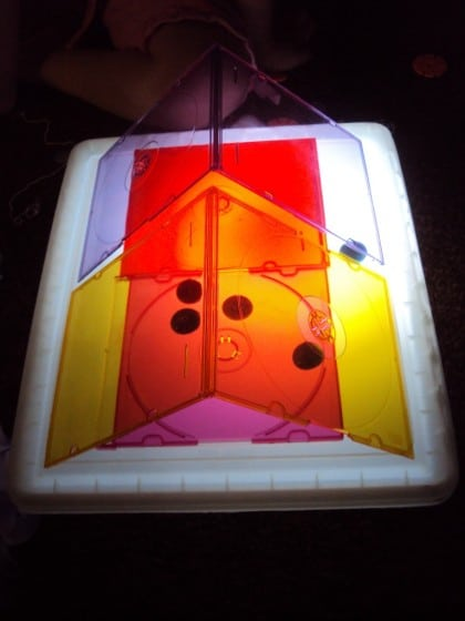 Playing with coloured CD cases on the homemade light box.