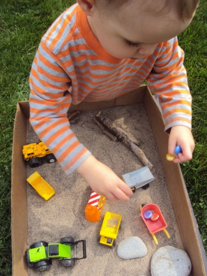 construction vehicles and glass beads in a cardboard box