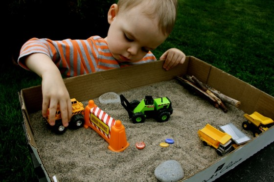 cars and trucks and sand in a cardboard box