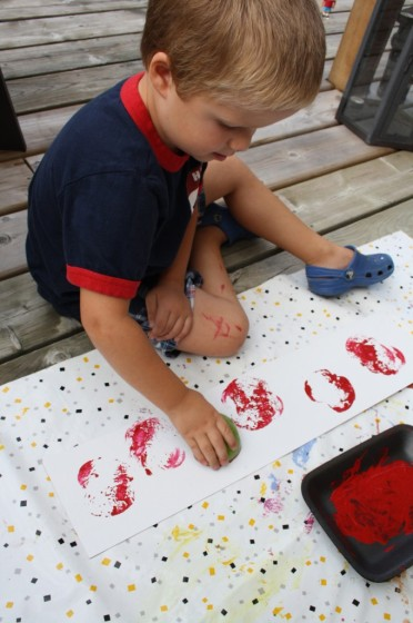 preschool boy stamping with apples