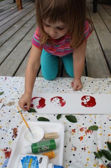 preschool girl gluing real leaf on apple stamping art