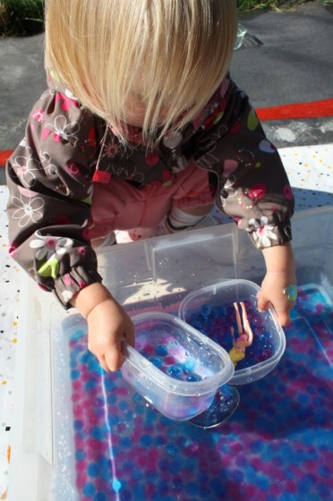 toddler playing with water beads sensory bin