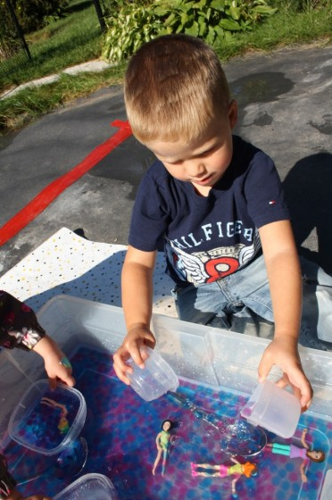 boy scooping water beads with containers