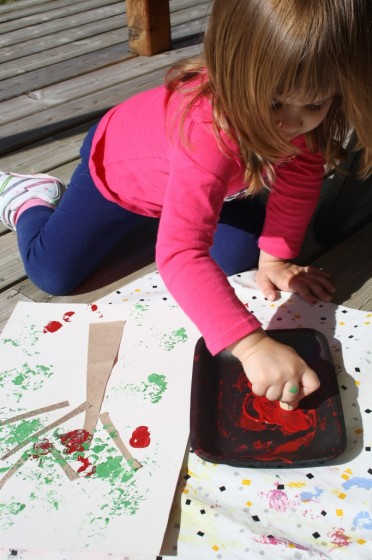 Child stamping with red paint