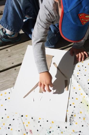 toddler using sandpaper to make an apple tree