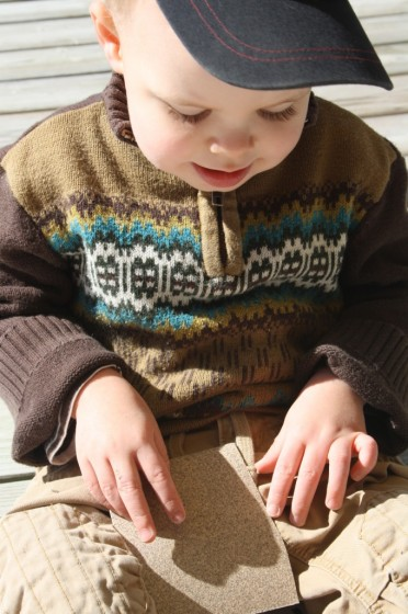 toddler examining sandpaper