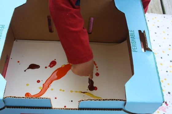 pouring paint on paper in a cardboard box