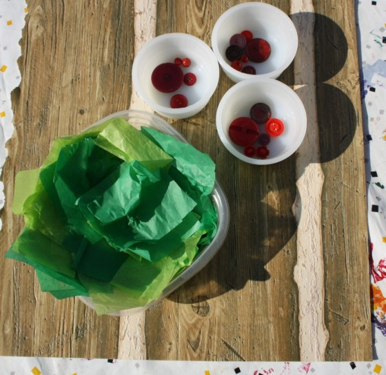 green tissue paper, red buttons, textured brown paper