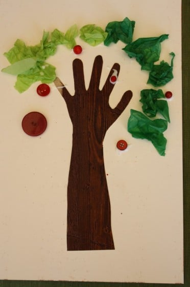 finished apple tree craft made with brown handprint, green tissue paper and red buttons