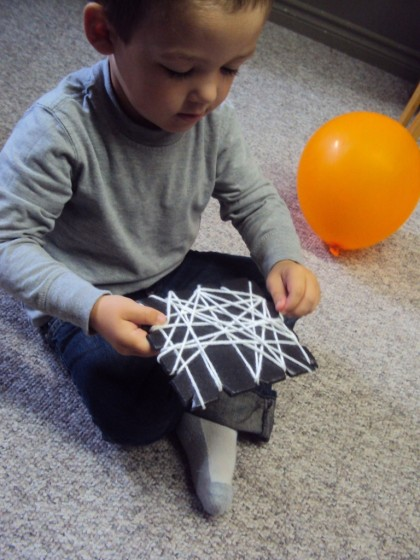 Toddler weaving yarn around a styrofoam produce tray