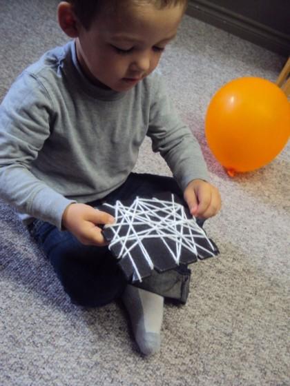 Toddler weaving yarn around a styrofoam produce tray