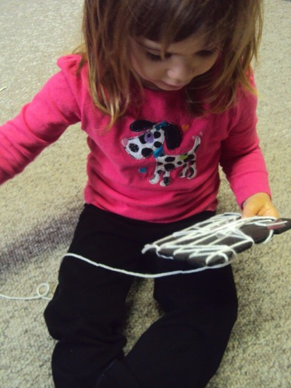 toddler weaving a spiders web with yarn