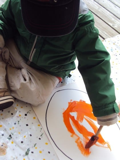 toddler painting a jack o lantern on white paper