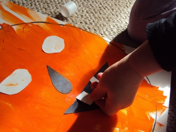 Preschooler gluing paper teeth on painted jack-o-lantern face