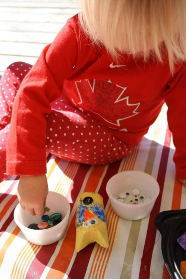 toddler making yellow owl with cardboard roll, fabric and buttons