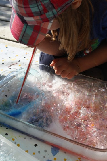 toddler blowing through straw into dish of coloured bubbles