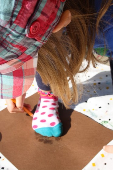 child tracing foot on construction paper for turkey body