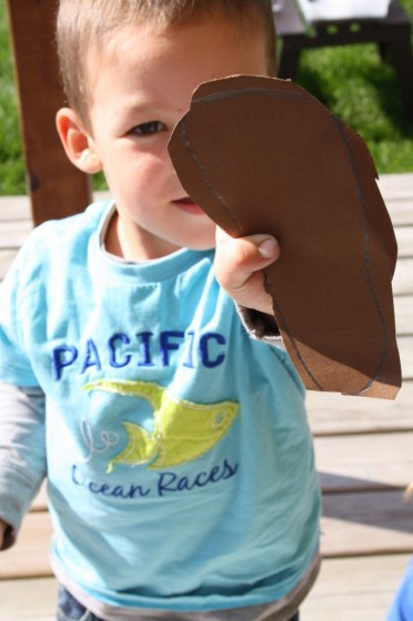toddler holding up footprint cut out of brown construction paper