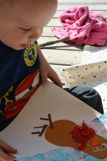 toddler boy admiring the turkey craft he made