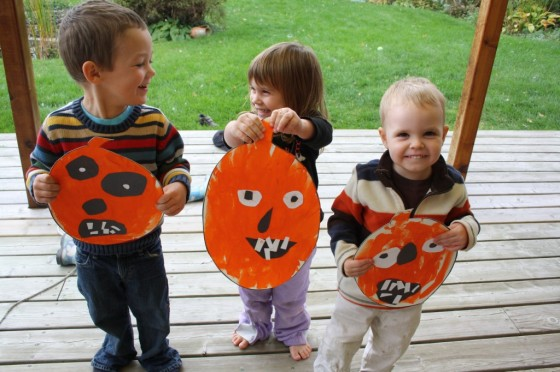 toddlers holding up painted jackolantern craft