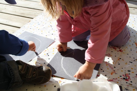 toddler drawing ghost on black construction paper
